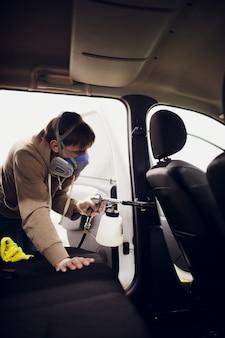 熱い蒸気で車を掃除するハンサムな男