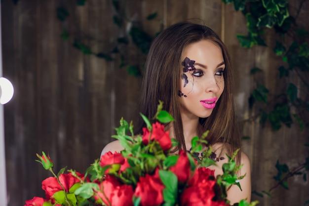 若い美しいきれいな女の子立っていると赤いバラのボックスを保持しています。立っている黒のエレガントなドレスで流行のファッションスタイルスタジオポートレート少女