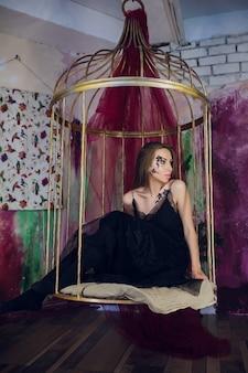 Фотомодель в фэнтезийном платье позирует стальная клетка