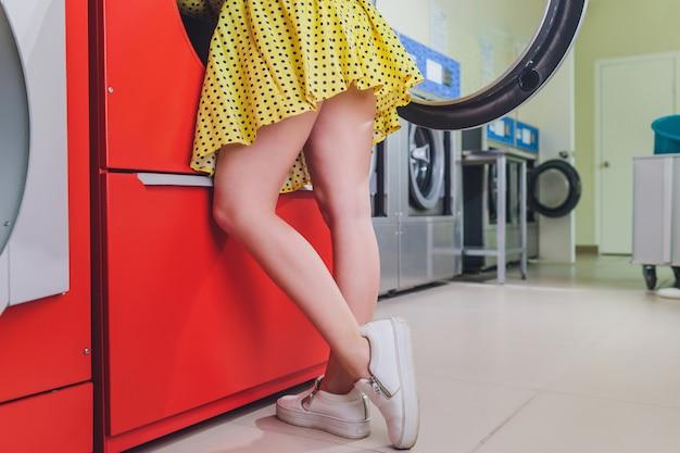 Женщина в ванной положить голову в стиральную машину.