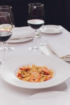 Паста баветта с жареными креветками, соусом бешамель, мяты, чеснок, помидоры, перец чили на белой тарелке, вид сверху, итальянская кухня.