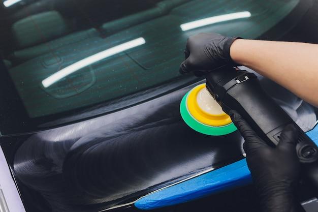 Детализация автомобиля - руки с орбитальной полировкой в автосервисе.