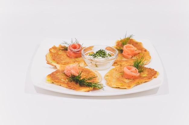 Тарелка с картофельными блинами, украшенными листьями базилика на столе.