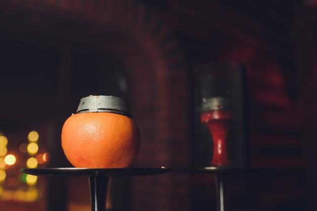 オレンジ色の高級水ギセル。フルーツのエキゾチックなボウル。水ギセルラウンジ。