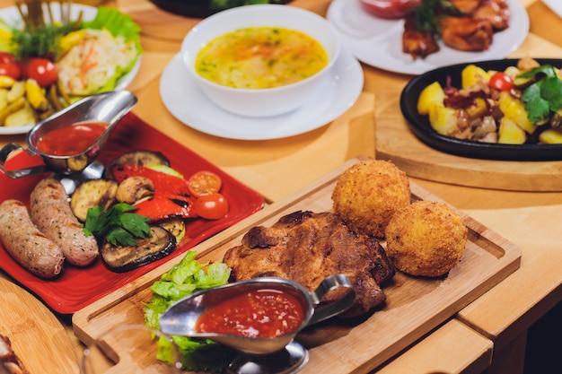 ディナーフードのコンセプト。グリルソーセージ、トルティーヤラップ、ビール飲料、素朴なスタイルの木製テーブルにさまざまな料理のディナーテーブル。