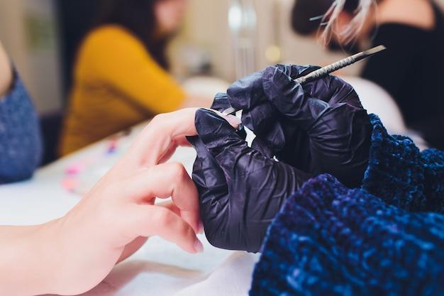 Руки в перчатках заботятся о мужских ногтях. маникюрный салон красоты.