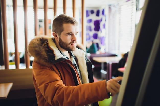 ファーストフード店で電子メニュー付きのタッチスクリーン端末で食べ物を注文する男性。