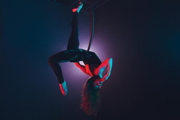 Воздушный акробат на ринге. молодая девушка выполняет акробатические элементы в воздушном кольце.