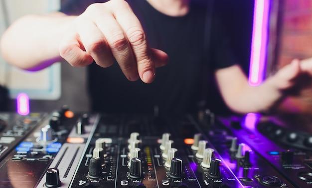 夜、ターンテーブルのレコードとコントロールスイッチのレコードの上に手を置いて、デッキで音楽をミキシングする男性のディスクジョッキーの手のクローズアップビュー。