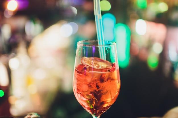 バーでカクテルをお楽しみください。バーテンダーはアペロールとスパークリングワインをグラスに注ぎます。