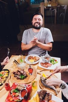 食物と一緒に大きなテーブルで男。