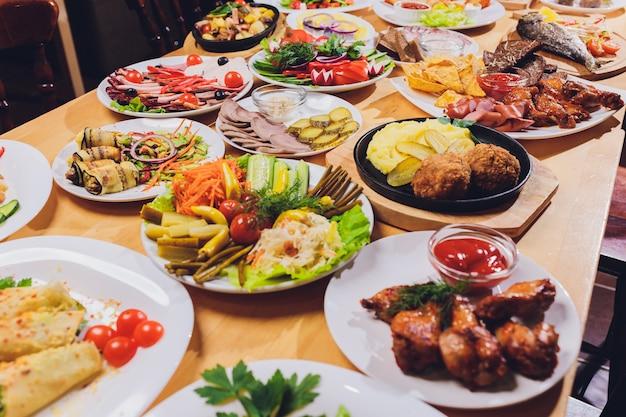 さまざまなスナックとサラダのあるダイニングテーブル。サーモン、オリーブ、ワイン、野菜、焼き魚のトースト。