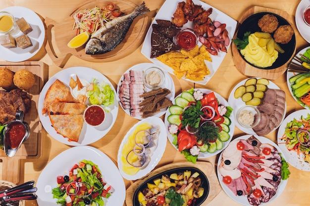 おいしいサラミ、スライスハム、ソーセージ、サラダが入ったフードトレイ。テーブルの選択と肉の盛り合わせ。