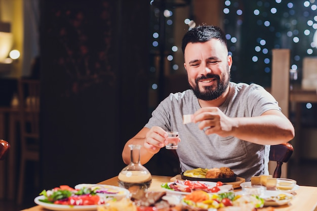 Мужчина пьет водку за большим столом с едой и жирными закусками.