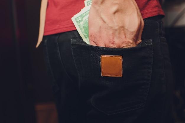 Бездомный человек держит долларовую купюру в руке. выборочный фокус на долларовой купюре.