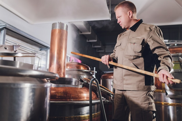 醸造所の醸造業者がタンクに麦芽を注ぎます。