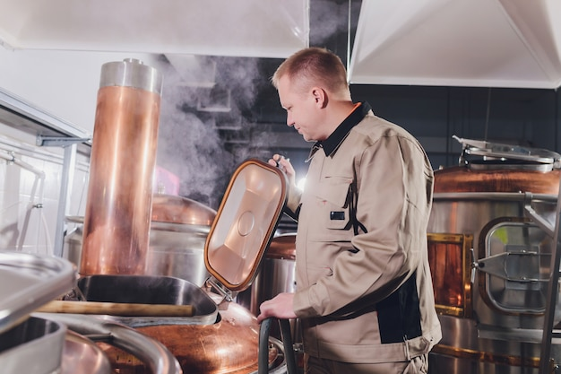 Пивовар в варочном цехе выливает солод в бак.