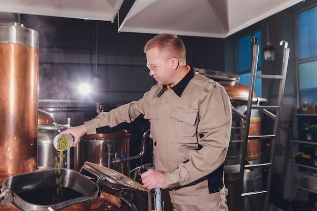 Пивовар с зеленым хмелем в фартуке и клетчатой рубашке на производстве. оценить качество ингредиентов пива.