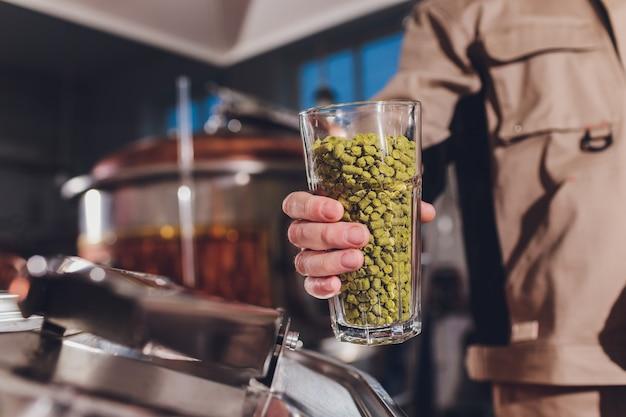 料理人の手で調味料とカップ。醸造用酵母。
