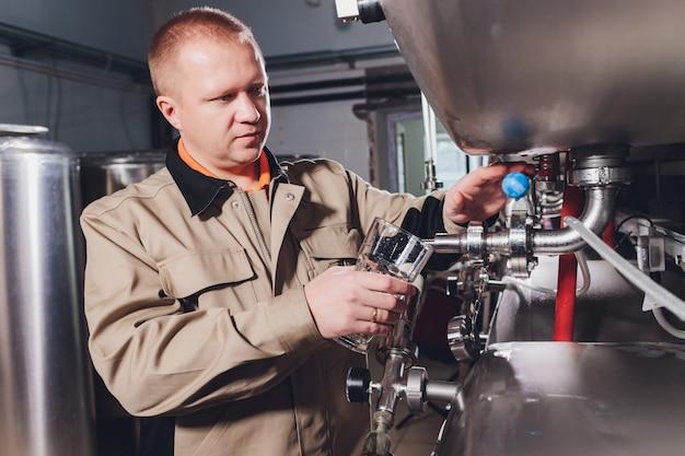 醸造所の男とエプロンは、醸造所のカウンターの後ろに立って、品質管理のためにグラスにビールを注ぎます。
