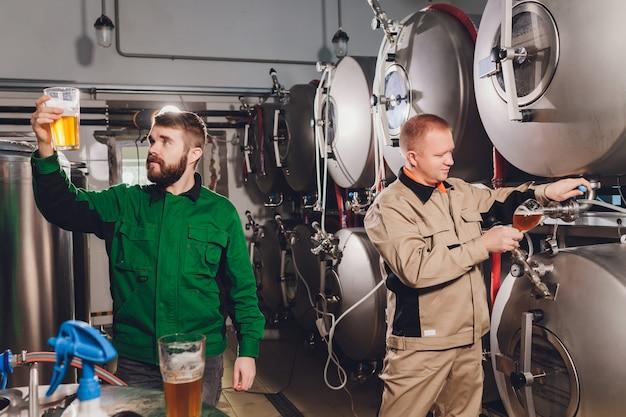 Зрелый человек, изучения качества ремесленного пива на пивоваренном заводе. инспектор работает на алкогольной фабрике, проверяет пиво. мужчина в винокурне проверяет контроль качества разливного пива.