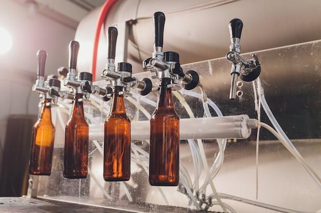 ビール醸造所の工場で、コンベアラインのガラス瓶にビールをこぼします。産業労働、食品および飲料の自動生産。工場での技術的作業。