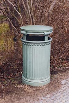 Чугунная серая урна стоит в осеннем парке.