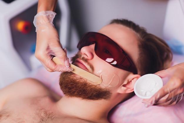 マスター医師は、レーザーでひげを生やした男性の永久に不要な顔の毛を除去する手順を実行します。美しさと健康。