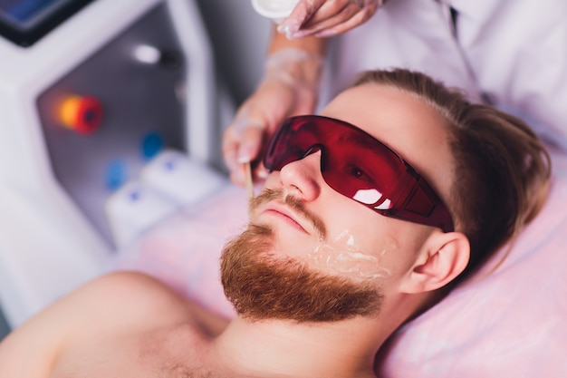 Мастер-врач проводит процедуру удаления навсегда нежелательных волос на лице у бородатого мужчины с помощью лазера. красота и здоровье.