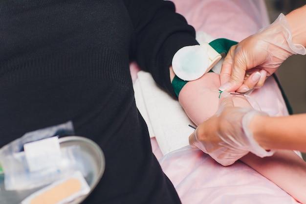 医師は注射器で血液を採取します。看護師は腕の静脈から血液を採取します。