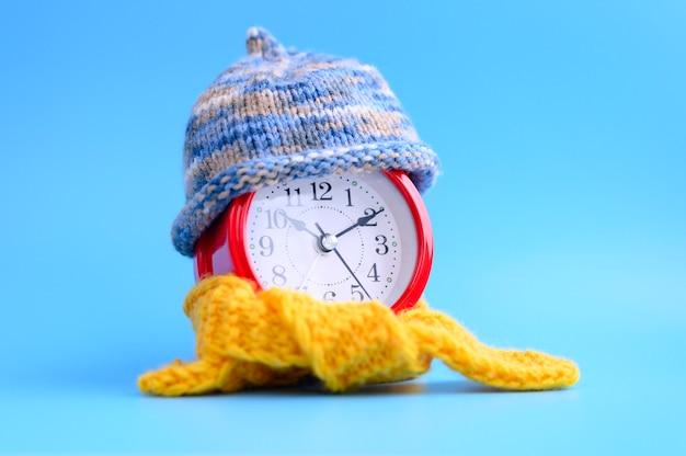 ニットウールの青い帽子と青を中心とした黄色のスカーフの赤い丸い目覚まし時計