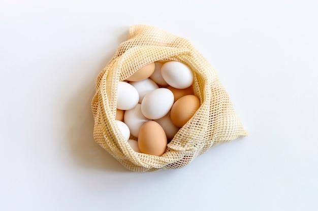 Куриные яйца белого и коричневого цвета в бежевой сетчатой сумке многоразового использования на белом столе. концепция фермерских продуктов, натуральное питание и защита окружающей среды