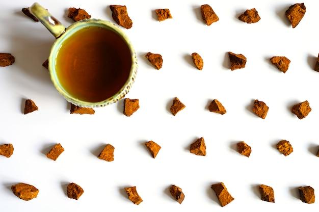 チャーガ茸とお茶。バーチツリーチャガキノコの破片と自然な薬用抗腫瘍と抗ウイルスデトックスティー、白い背景で隔離の醸造。