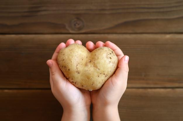 Некрасивая еда. детские руки, держа уродливый овощ картофель в форме сердца на деревянный стол.