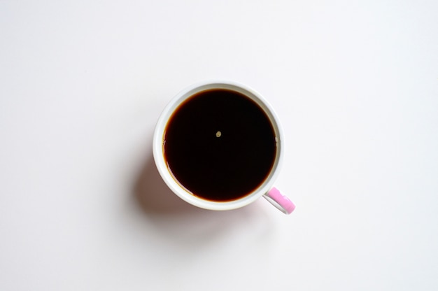 白い背景に分離された白樺チャガきのこから醸造された黒または濃い茶色の豊富なチャガティーカップ。
