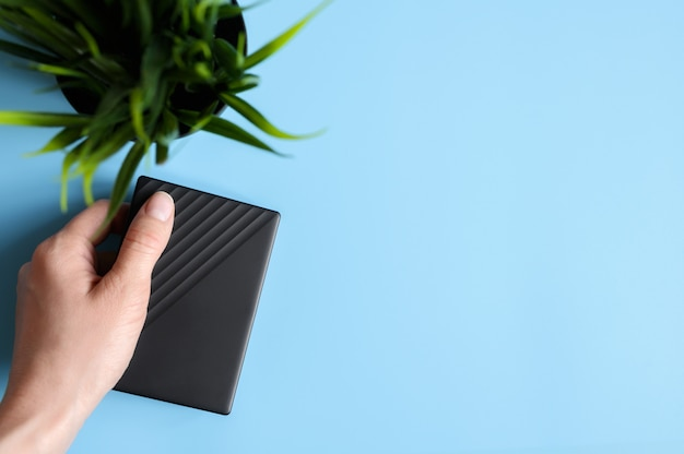 外付けハードドライブは、女性の手では黒で、青の背景に緑の植物です。テキスト用のスペース