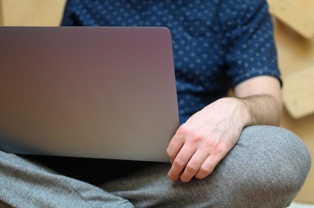 自宅でラップトップを使用して作業する男性