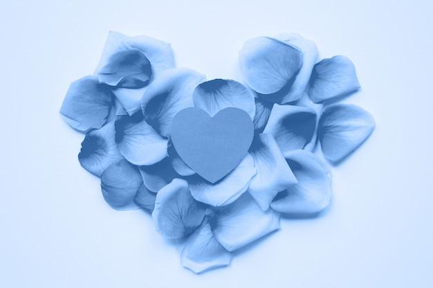 聖バレンタインデー。心はバラの花びらの背景に紙から切り取られます。