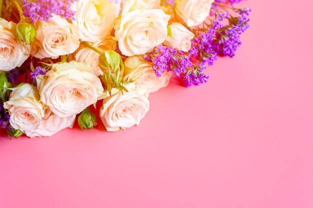 Букет кремовых роз и ярко-фиолетовых цветов в полном расцвете на розовом