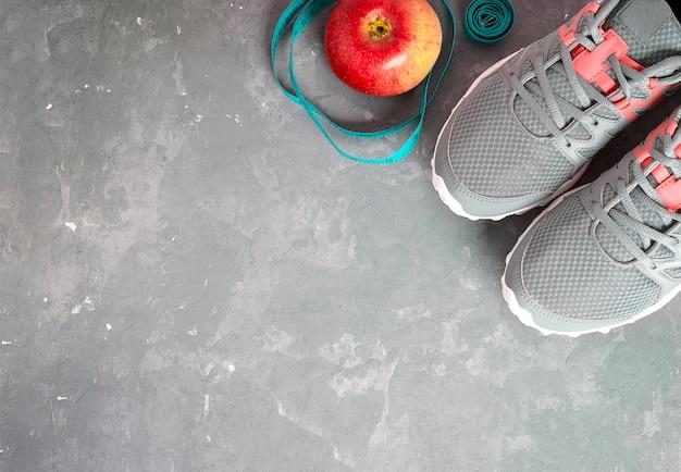 Серые кроссовки, яблоко на сером фоне. фитнес фон