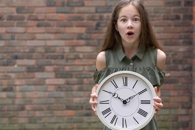 時計、コピースペースで心配している少女。遅刻、時間は最も貴重な資源の概念です