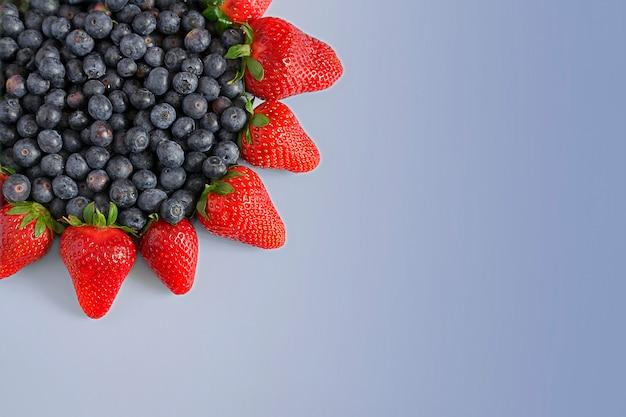 青色の背景にイチゴとブルーベリーのフレーム。トップビュー、コピースペース。