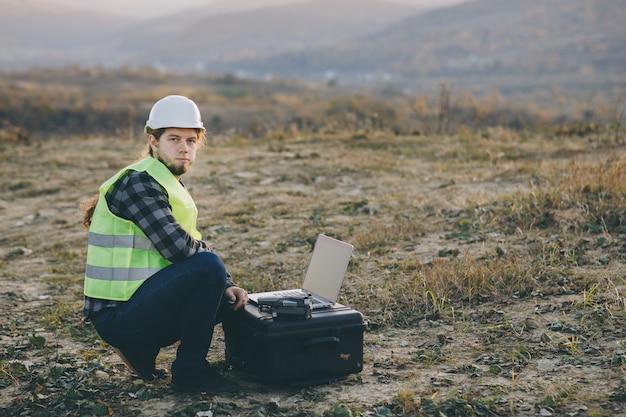 ハード帽子の産業エンジニアは、タッチスクリーンのラップトップを使用しています。彼は重工業工場で働いています。