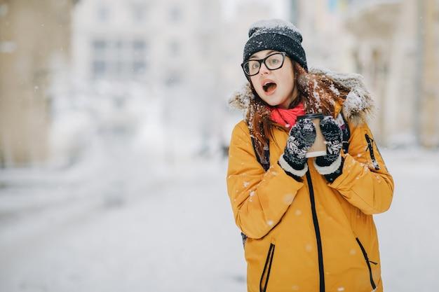 美しい少女は、雪の降る冬の周りを見てコーヒーを飲む