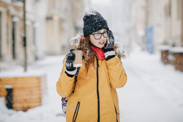 Девушка пьет кофе и разговаривает по телефону на улице в зимний период