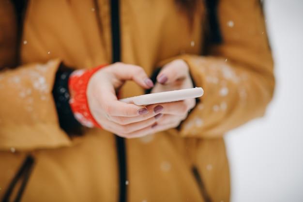 Руки держат смартфон с светящегося экрана. хипстер девушка текстовых сообщений на смартфон мобильный в зимней природе