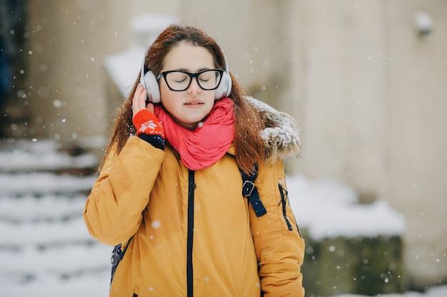 魅力的な若い女の子が街に行き、電話で音楽を聴きます。スタイリッシュな外観、カジュアルなアクセサリー。トレンディな外観