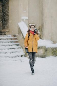 Портрет красивой девушки. прослушивание музыки в снежном городе