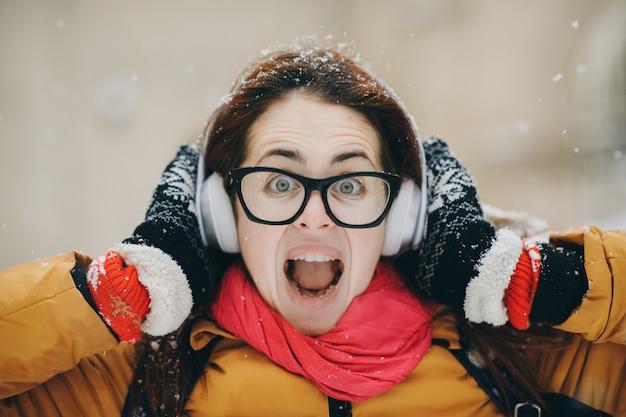 冬の森を歩くと音楽を聴く美しい若い女性。ライフスタイル、冬のファッション、美容