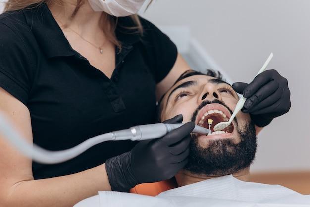 歯科医院で。クリニック、クローズアップで患者の歯を調べる歯科医